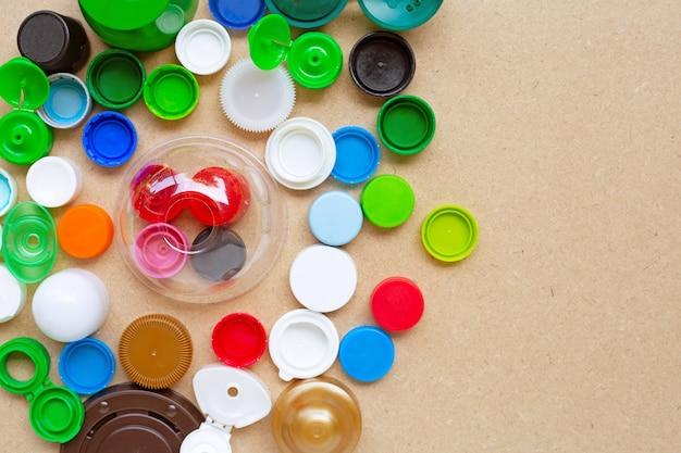 Tappi di bottiglia di plastica variopinti e coperchio di vetro di plastica su compensato