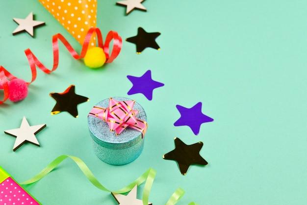 Tappi di compleanno e un regalo, coriandoli su un tavolo verde