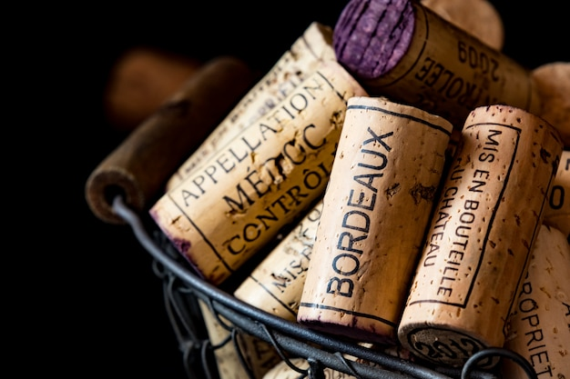 Tappi di sughero vecchio di vini francesi in un cesto di filo