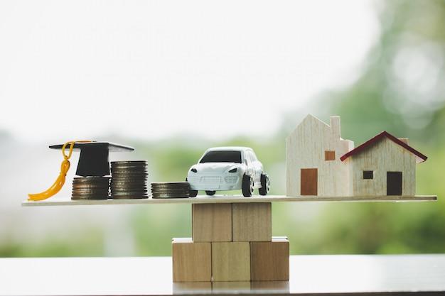 Tappo di laurea auto casa sul blocco di legno, concetto educare laureato