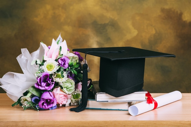 Tappo di laurea, cappello con carta di laurea e bouquet di fiori sul tavolo di legno.