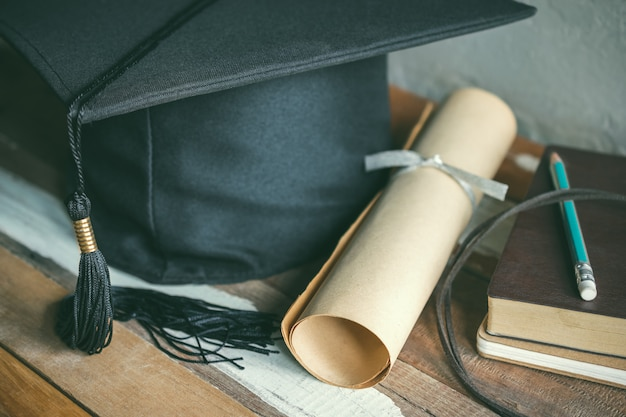 Tappo di laurea, cappello con carta di laurea sul concetto di graduazione di tabella di legno.