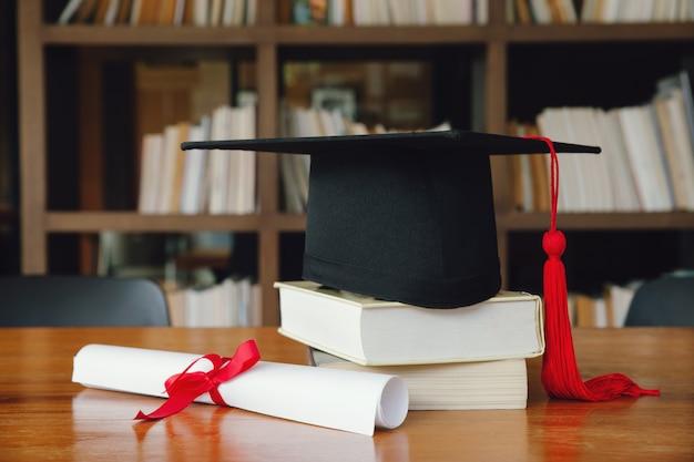Tappo di laurea nero con laurea sul tavolo di legno nella libreria. laurea