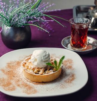 Tarte di mele porzionata con gelato alla vaniglia, su tovaglia viola