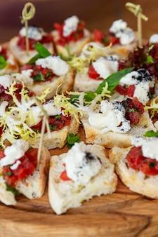 Tartine appetitose su una tavola di legno. snack a buffet. avvicinamento. verticale.
