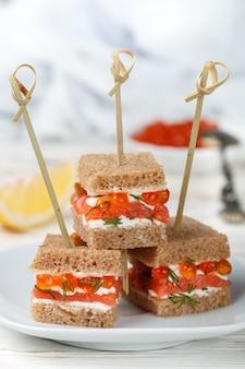 Tartine di pane di segale con salmone affumicato, formaggio a pasta molle, aneto e caviale