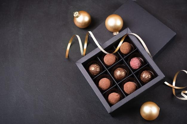 Tartufi al cioccolato di lusso in una scatola nera su uno sfondo nero con decorazioni natalizie palline dorate e serpentine. una scatola di cioccolatini fatti a mano per natale.