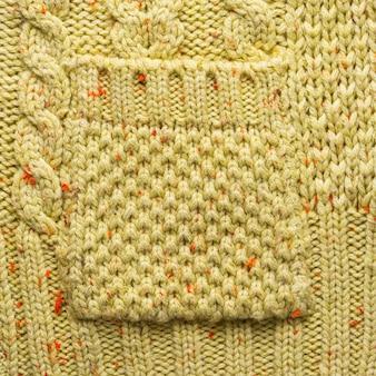 Tasca lavorata a maglia su uno sfondo di maglione lavorato a maglia