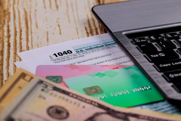Tassa federale 1040 forma con tastiera del computer e dollari americani