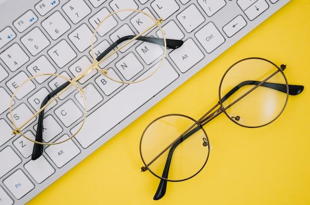 Tastiera bianca e un paio di occhiali su sfondo giallo