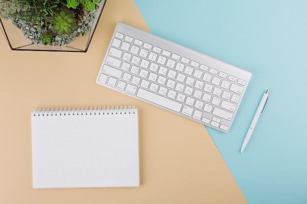 Tastiera con quaderno bianco e pianta