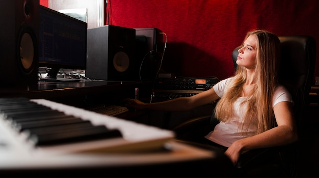 Tastiera del primo piano e donna vaga in studio