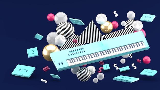 Tastiera di piano blu e nastro blu in mezzo delle palle variopinte sul blu. rendering 3d