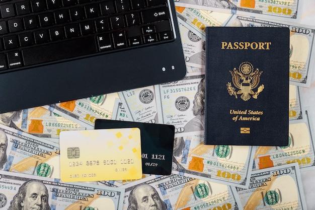 Tastiera di tecnologia e internet, centinaia di banconote da un dollaro per l'acquisto di un biglietto online con carta di credito sul passaporto americano