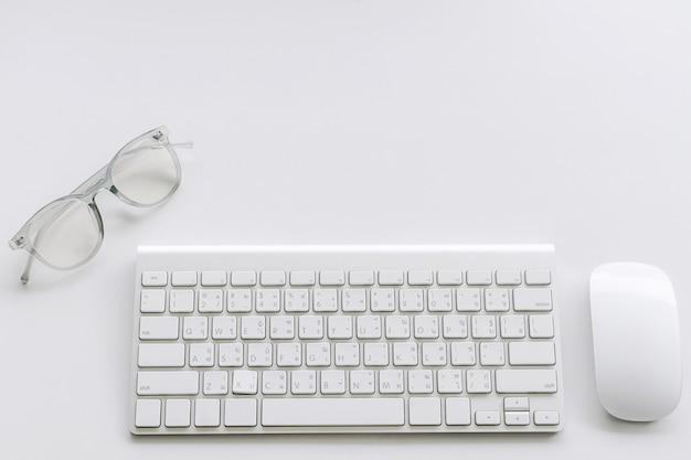 Tastiera e mouse di calcolatore con i vetri su priorità bassa bianca