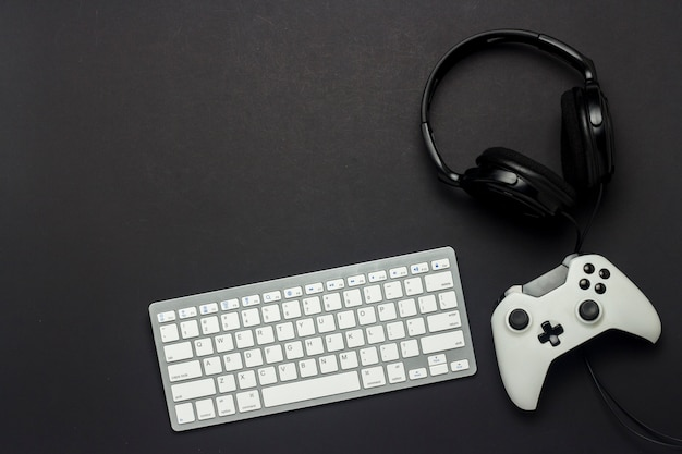 Tastiera, gamepad e cuffie su sfondo nero. il concetto del gioco sulla console, il gioco. vista piana, vista dall'alto.