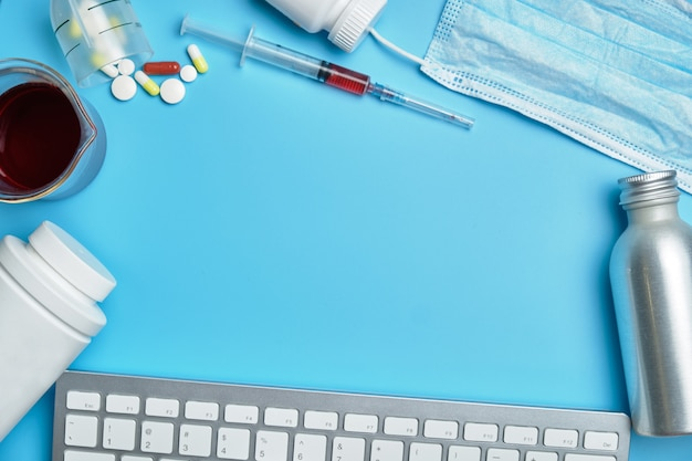 Tastiera, lattine bianche, siringa, maschera protettiva su sfondo blu