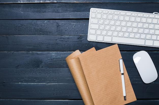 Tastiera, mouse e taccuino sulla scrivania scura