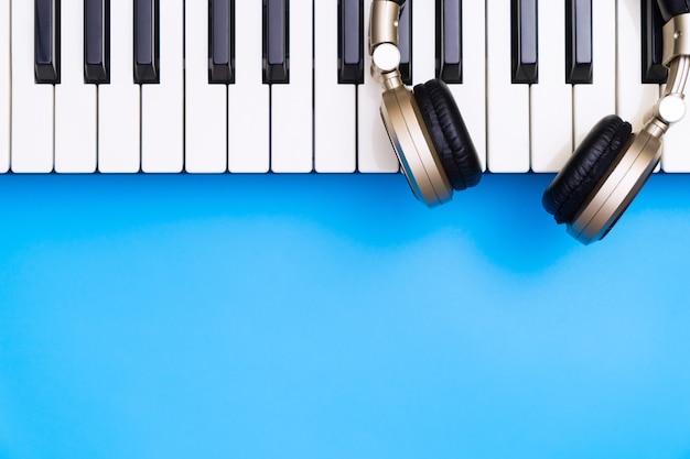 Tastiera musicale con cuffia dorata per lo spazio blu della copia qui sotto