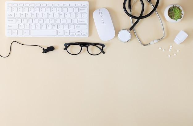 Tastiera, stetoscopio, microfono e altre forniture vista dall'alto. consultazione in linea del medico e concetto di comunicazione medica a distanza