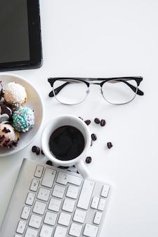 Tastiera vicino a tazza, occhiali e biscotti sul piatto