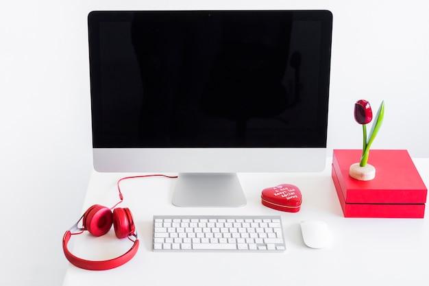 Tastiera vicino al monitor, mouse del computer e cuffie sul tavolo
