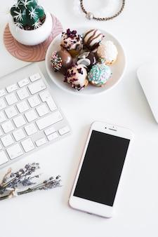 Tastiera vicino smartphone, bracciali, mouse del computer e biscotti sul piatto