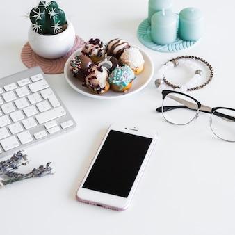Tastiera vicino smartphone, candele, occhiali e biscotti sul piatto