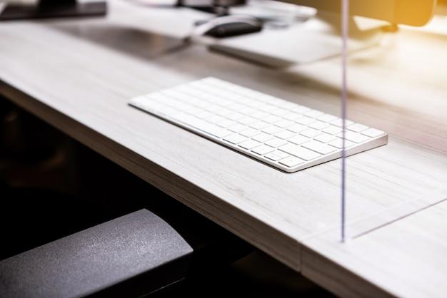 Tastiera wireless con separatore in plexiglass acrilico posizionato sulla scrivania della postazione di lavoro