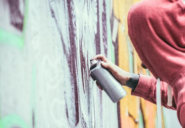 Tatuatore di graffiti che dipinge con spruzzi di colore la sua immagine scura sul muro. artista contemporaneo al lavoro