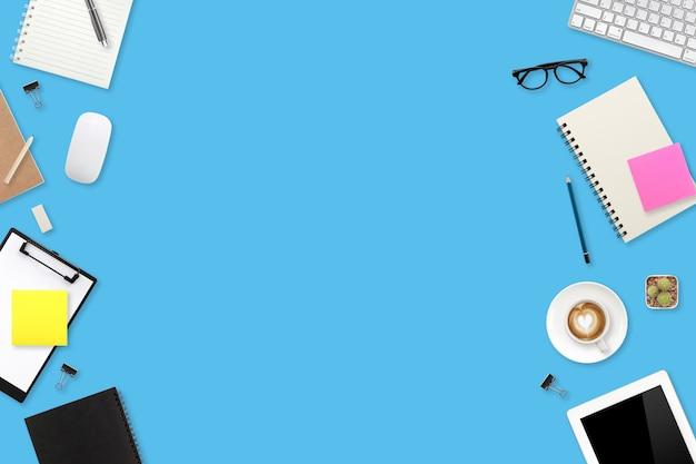 Tavola blu di affari dell'area di lavoro di vista superiore con il computer portatile, gli articoli per ufficio e la tazza di caffè facendo uso di per