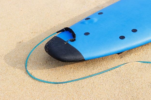 Tavola da surf blu che si trova sulla vista laterale del primo piano della sabbia