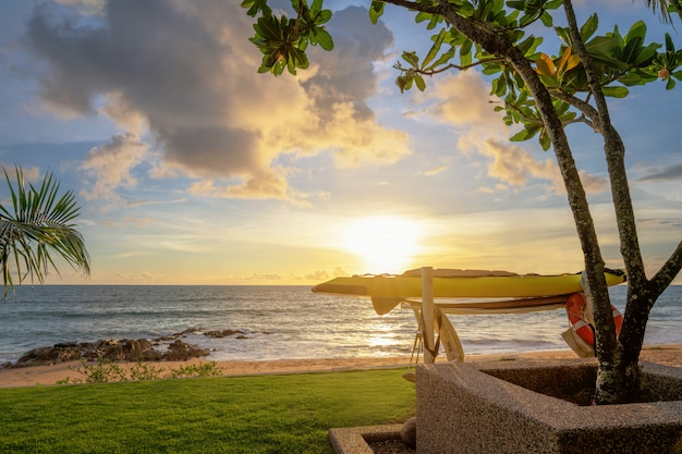 Tavola da windsurf e bagnino di colorato tramonto sul mare. sabbia e palme