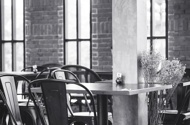 Tavola del primo piano nel tono del fondo di vista della caffetteria in bianco e nero