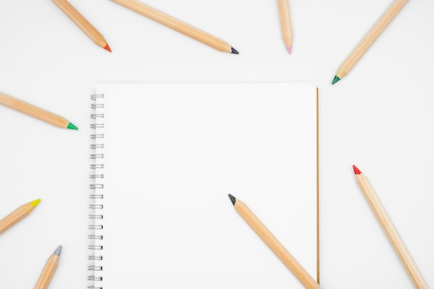 Tavola dell'ufficio con il taccuino e la matita, vista superiore, disposizione piana con fondo bianco