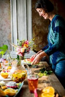 Tavola della donna che mette frutti e bevande per la festa
