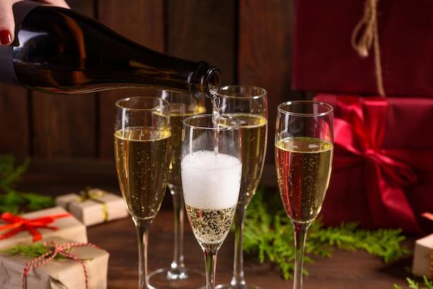Tavola delle vacanze di natale con bicchieri e una bottiglia di vino di champagne