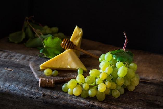 Tavola di ardesia con formaggio. formaggio e uva su legno con miele. concetto di prima colazione. ancora lif