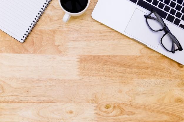 Tavola di disposizione piana della scrivania del posto di lavoro moderno con il computer portatile su legno