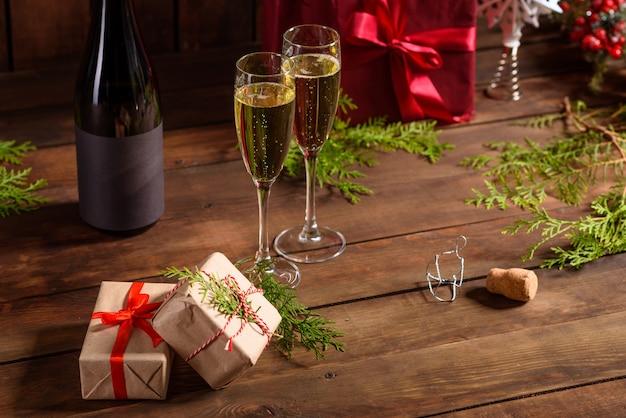 Tavola di festa di natale con bicchieri e una bottiglia e regali