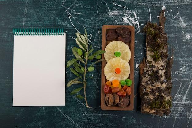 Tavola di frutta secca e gelatinosa con un pezzo di legno e un taccuino da parte