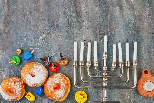 Tavola di hanukkah che mette un candeliere con le candele, la ciambella e le trottole sul blu