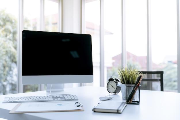 Tavola di lavoro bianca moderna dello scrittorio con il computer portatile del computer e stazionario in ministero degli interni