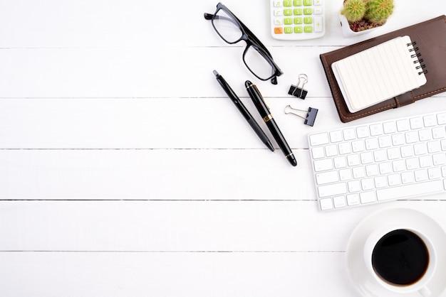 Tavola di legno bianca della scrivania con il taccuino in bianco, calcolatore della tastiera di computer, tazza di caffè