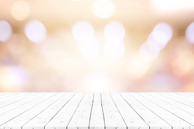 Tavola di legno bianca di prospettiva sulla cima sopra lo sfondo naturale della sfuocatura.