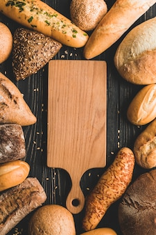 Tavola di legno circondata da pagnotte di pane