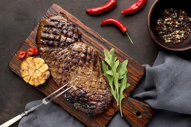 Tavola di legno con carne alla griglia e condimento