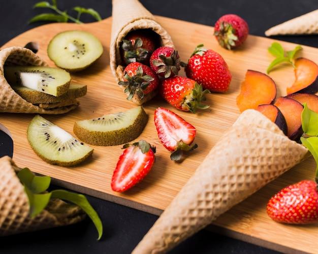 Tavola di legno con coni gelato con frutta