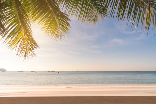 Tavola di legno con l'albero di cocco e tramonto alla spiaggia tropicale, concetto di vacanze estive
