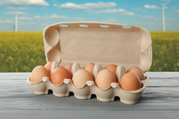 Tavola di legno con le uova in contenitore di cartone contro il campo. concetto di agricoltura